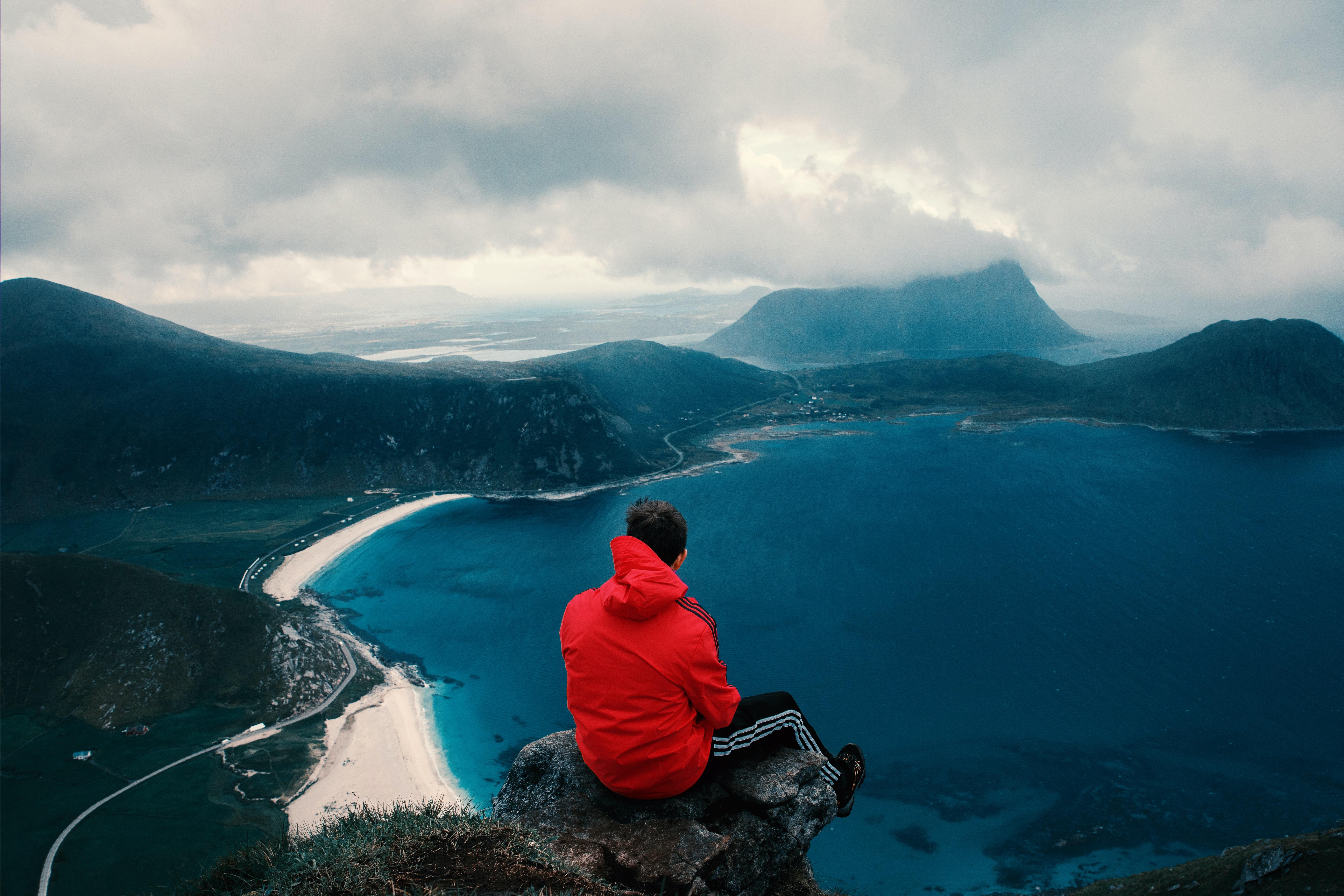 Gutt sitter på en klippe og ser på havet
